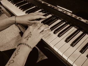 tattooed hands playing piano